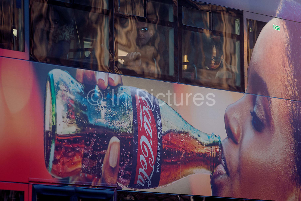 Commuters sit on the top deck of a London bus with an ad for Coca-Cola on the side as it travels through Westminster, on 18th January 2017, in Parliament Square, London England.