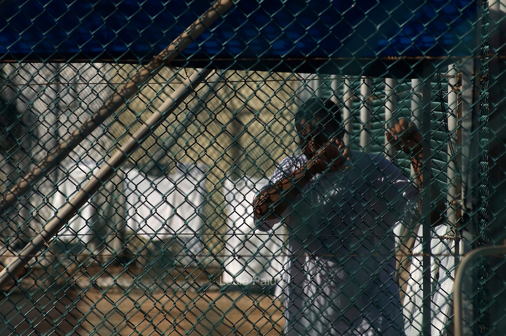 """A detainee clutches a fence at Camp 4 at the detention facility in Guantanamo Bay, Cuba. Camp 4 is a communal style camp where more compliant detainees live in small groups and have access to a more open air environment. Approximately 250 """"unlawful enemy combatants"""" captured since the September 11, attacks on the United States continue to be held at the detention facility.(Image reviewed by military official prior to transmission)"""