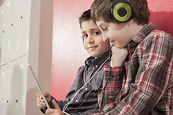 Schoolboys listening to music and watching video in corridor near lockers, Bavaria, Germany