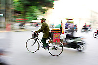 Man riding a bike in the traffic of Hanoi.