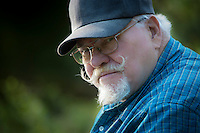 portrait of a senior man with goatee, glasses, and ballcap, looking at the camera while fishing at a beaver pond in rural Kitsap County, Washington, USA