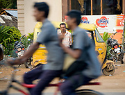 Indian man rickshaw driver looking at the camera whilst two men rush past on a bike, street scene Tanjore, Tamil Nadu, India . .