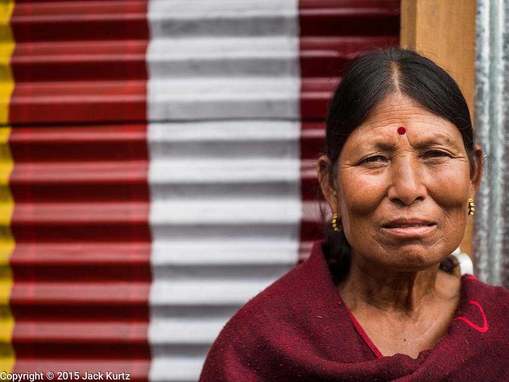 02 AUGUST 2015 - BHAKTAPUR, NEPAL:  A woman in a small Internal Displaced Person (IDP) camp at Durbar Square in Bhaktapur for people left homeless by the Nepal earthquake. The Nepal Earthquake on April 25, 2015, (also known as the Gorkha earthquake) killed more than 9,000 people and injured more than 23,000. It had a magnitude of 7.8. The epicenter was east of the district of Lamjung, and its hypocenter was at a depth of approximately 15km (9.3mi). It was the worst natural disaster to strike Nepal since the 1934 Nepal–Bihar earthquake. The earthquake triggered an avalanche on Mount Everest, killing at least 19. The earthquake also set off an avalanche in the Langtang valley, where 250 people were reported missing. Hundreds of thousands of people were made homeless with entire villages flattened across many districts of the country. Centuries-old buildings were destroyed at UNESCO World Heritage sites in the Kathmandu Valley, including some at the Kathmandu Durbar Square, the Patan Durbar Squar, the Bhaktapur Durbar Square, the Changu Narayan Temple and the Swayambhunath Stupa. Geophysicists and other experts had warned for decades that Nepal was vulnerable to a deadly earthquake, particularly because of its geology, urbanization, and architecture.      PHOTO BY JACK KURTZ