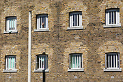 A hand waves from a cell window of D wing Wandsworth Prison. HM Prison Wandsworth is a Category B men's prison at Wandsworth in the London Borough of Wandsworth, South West London, United Kingdom. It is operated by Her Majesty's Prison Service and is one of the largest prisons in the UK with a population over 1500 people. (photo by Andy Aitchison)