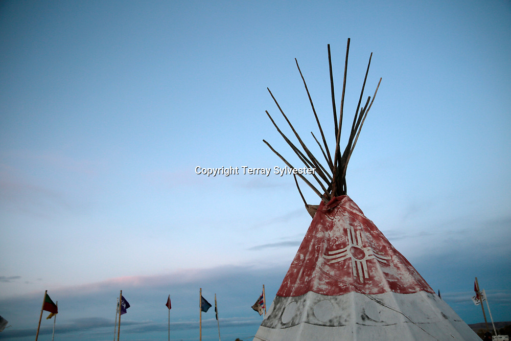 A tipi and tribal flags catch the evening light in the opposition camp against the Dakota Access oil pipeline on October 4, 2016. Cannon Ball, North Dakota, United States.