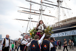 © Licensed to London News Pictures. 01/04/2013. London, UK. Sophie Macionczyk of Poland is lifted into the air on a chair by members of the Blackheath Morris Men as part of an Easter ritual in Greenwich, London, today (01/04/2013).  The tradition, known as 'Easter Lifting', involves the lifting of a female volunteer into the air three times before being asked to kiss each of those doing the lifting.  Photo credit: LNP