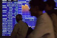 Tokyo, Japan - November 9, 2016: Pedestrians near Tokyo Station check out and a bank's financial stock and currency quote board after it was announced Donald Trump won the the US presidential election by defeating Hillary Clinton. Financial markets around the world went into a tailspin as did currency exchange rates. In Japan the US dollar dropped rapidly from around 105 yen to a dollar to 101 yen by midday. The Nikkei 225 index also nose-dived by 5.36 ending down 919.84 points from the previous at 16,251.54. (Torin Boyd/Polaris).