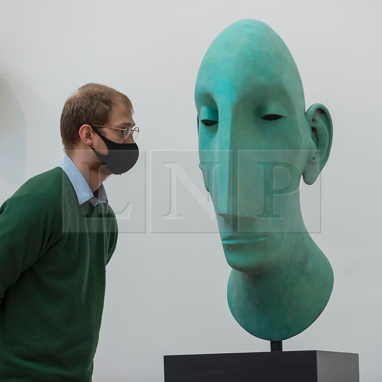 """© Licensed to London News Pictures. 28/09/2020. LONDON, UK. A staff member views """"Head II"""" by Tim Shaw, RA.  Preview of the Summer Exhibition at the Royal Academy of Arts in Piccadilly which, due to the Covid-19 lockdown, is taking place for the first time in the autumn.  Over 1000 works in a range of media by Royal Academicians, established and emerging artists, feature in the exhibition which runs from 6 October 2020 – 3 January 2021.  Photo credit: Stephen Chung/LNP"""
