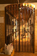 An iron gate leading in to the private wine cellar with aging bottles. Bodega Pisano Winery, Progreso, Uruguay, South America