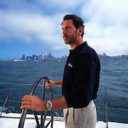 Larry Ellison, owner of several superyachts, founder of Oracle, and the depending on its flucuating stock price he is sometimes the second to fourth richest man in the world.  He is helming his racing yacht Sayonara in San Francisco Bay.