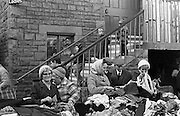 It's a free for all as elderly pensioners sift through piles of clothing left outside a community hall at a 1986 jumble sale in the south Wales town of Abergavenney, Monmouthshire. Some hold up items of clothing and others are happy to stand back and watch while some young children descend some steps of this Victorian-era building during a charity event held by the local Lions club, whose volunteers help the elderly and the disadvantaged within their community. Property has been donated and the old folks' attention is on their finds which are within their price range, having to survive on meagre pensions.