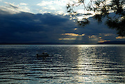 Small boat, with rays of setting sun streaming through clouds onto water. Makarska, Croatia