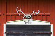 Traditional style Swedish wooden painted house. Black door. Barn Date 1929 painted over the door and big elk moose antlers. Smaland region. Sweden, Europe.
