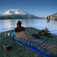 CHINA, Xinjiang Province. Mark Newcomb<br /> (MR) wakes from bivouac by Lake Karakul in Pamir Mts. 7546m Mustagh Ata bkg.