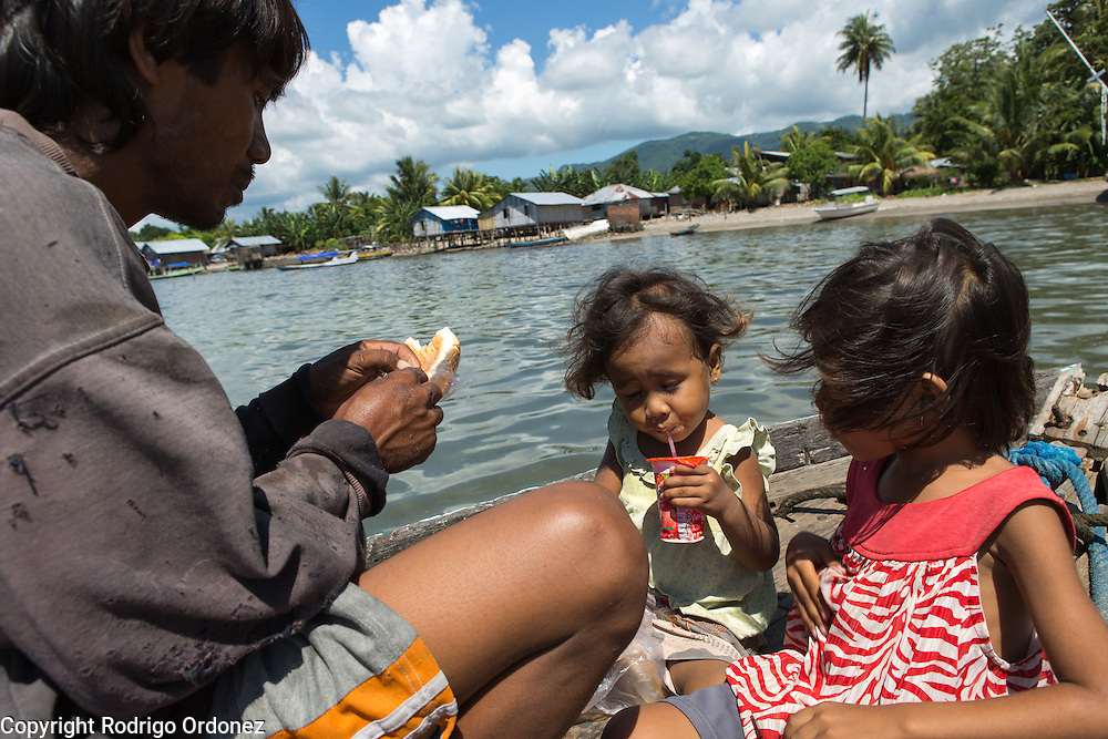 Siti Rofi'ah's son-in-law Jainudin One, 41 (left), eats a snack in his boat with his daughters (from left to right) Kesha, 4; and Refa, 6. Jainudin just returned home after fishing overnight. He and his family live in Lewoleba, Nubatukan subdistrict, Lembata district, East Nusa Tenggara province, Indonesia.