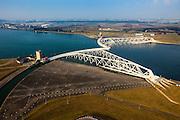 Nederland, Zuid-Holland, Nieuwe Waterweg, 19-09-2009; Functioneringssluiting Maeslantkering: de waterkering in de Nieuwe Waterweg wordt een maal per jaar, voordat het stormseizoen begint, getest. Tijdens  het sluiten van de kering ligt alle scheepvaartverkeer naar de Rotterdamse haven stil. De eigenlijk kering bestaat uit twee (holle) kerende wanden die nadat ze op hun plaats zijn gebracht, afgezonken worden door er water in te pompen. In de voorgond een van de dokken waar de wand normaal gesporken in opgeborgen is. <br /> De Maeslantkering sluit normaal gesproken alleen bij dreigende stromvloed en bij een waterstand van 3 meter of meer boven NAP. De kering, onderdeel van de Deltawerken, vormt samen met de Hartelkering de Europoortkering en beschermt Rotterdam en achterland bij extreme waterstanden. <br /> Netherlands, Hoek van Holland - Rotterdam harbour. Aerial view of the new storm surge barrier (Maeslantkering) in the Nieuwe waterweg during the so-called functioning closure, taking place one a year before the storm season begins. The waterway, leading to the Port of Rotterdam, is closed during the test.<br /> luchtfoto (toeslag), aerial photo (additional fee required)<br /> foto/photo Siebe Swart