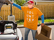 "11 MAY 2020 - DES MOINES, IOWA: JERRY CLUTTS puts food packages into a client's car at a ""no touch"" emergency food pantry at DSM First Church in Des Moines. The emergency pantry at DSM First Church expanded from distribution one day a week to three days per week after the COVID-19 pandemic forced the closure of many Iowa businesses. Food banks and emergency pantries in Iowa continue to see increased demand for services, even though the governor is reopening the state's economy. Iowa's unemployment rate for April hasn't been released yet, but based on national trends, it is expected to soar to well over 10% from 3.8& in March. COVID-19 infections continue to skyrocket. On Monday, 11 May, the governor announced that 12,373 people tested positive for coronavirus (SAR-CoV-2) and  271 had died.              PHOTO BY JACK KURTZ"