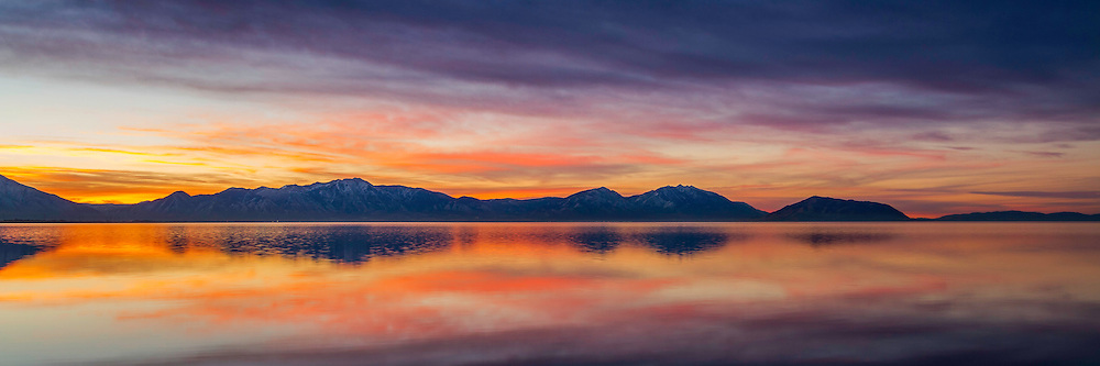 A calm scene over Utah Lake as the sun rises and colors flow through the sky.