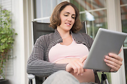 Pregnant woman holding tablet computer smiling