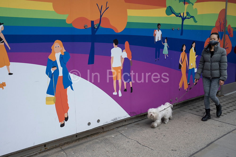 Woman walking her dog interacts with figures on a hoarding outside a shop being refitted on the Kings Road in the upmarket area of Chelsea on 14th April 2021 in London, United Kingdom. Chelsea is one of the principal areas for mid-range, exclusive or luxury goods in West London. It is known as a district where the rich and wealthy shop, mostly for high end ad well as high street fashion and jewellery.