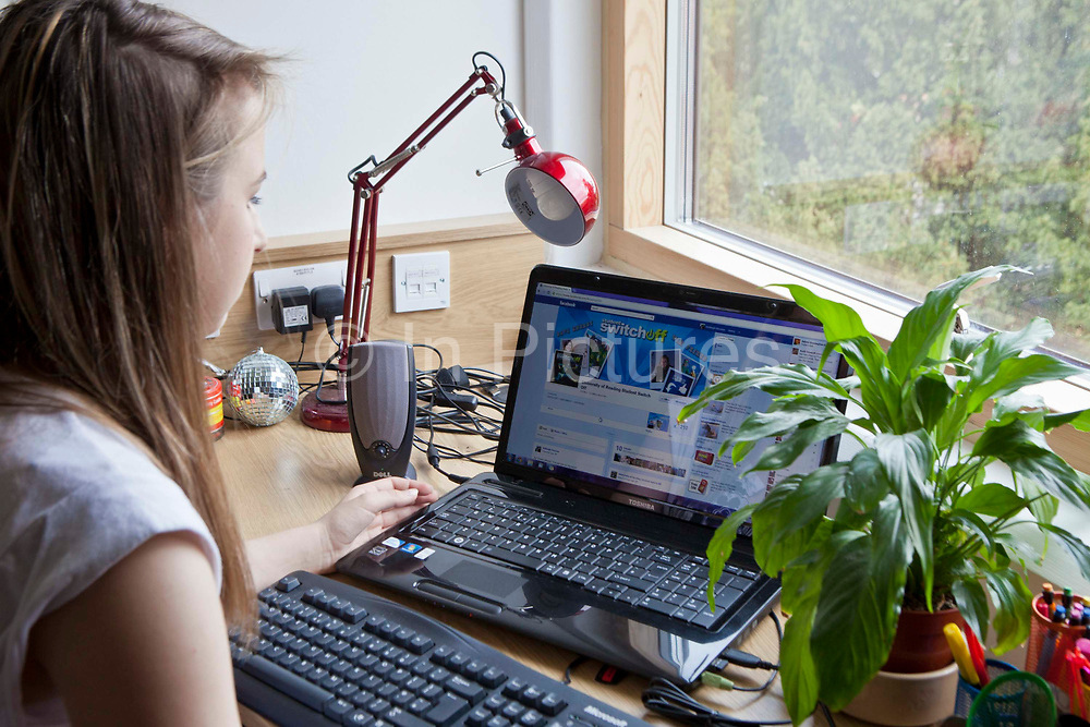 A student at Reading University on her laptop visits a website. The Student Switch Off website is encouraging students to take simple steps to save energy, including wrapping up warm, switching off lights and using lids on saucepans. Reading, UK.
