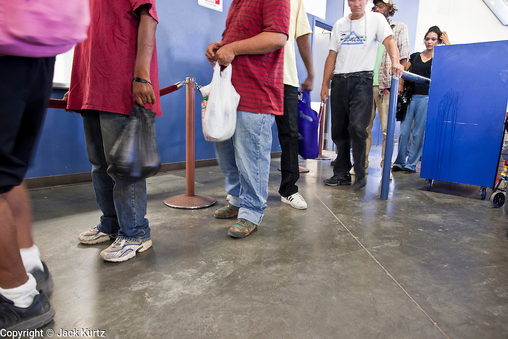 """Sept. 27 - PHOENIX, AZ: People wait in line for lunch in the dining room at the Society of St. Vincent de Paul in Phoenix.  September 27, 2010 is the 350th Feast Day of Saint Vincent de Paul, also known as the """"Apostle of Charity."""" To mark the day, the Society of St. Vincent de Paul in Phoenix served birthday cake during the lunch service. The US Census office recently announced that poverty in the US has spiked to 14.3% of the population, the highest poverty rate since 1994. Officials at St. Vincent de Paul in Phoenix said that demand for their services have increased steadily in the last three years. They currently feed about 1,100 people, either homeless or members of the working poor, every day.    Photo by Jack Kurtz"""