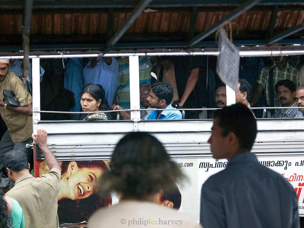 Passengers queue to board a bus, Cochin, Kerala, India