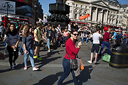 Tourist guide shepherding her group of tourists through Piccadilly Circus, London, UK.