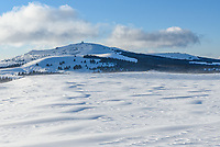 Snow drifts blow across a treeless meadow in the Bighorn Mountains. In the distance is Medicine Mountain. The Medicine Wheel at the top was built by Native Americans thousands of years ago, and there is also an FAA radar used to track flights.