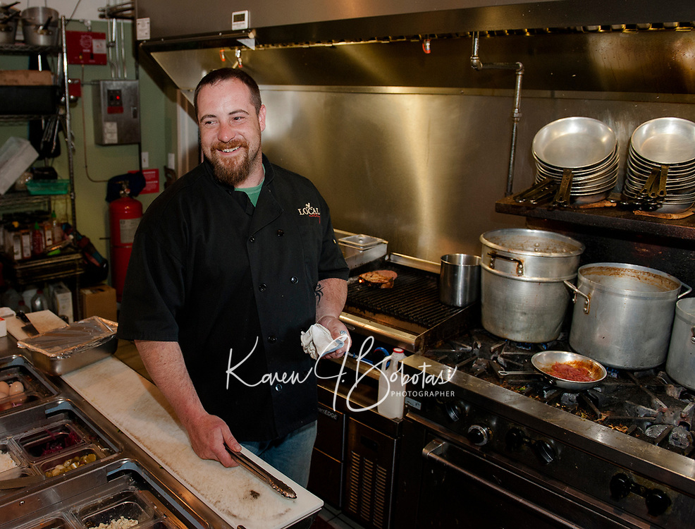 """Chef Kevin Halligan prepares a house-raised smoked pork chop with potato latkes, parsnip apple puree and red onion jam during """"Restaurant Week"""" at The Local Eatery Tuesday evening.   (Karen Bobotas/for the Laconia Daily Sun)"""