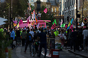 Environmental activists from Extinction Rebellion gather around a giant pink table used to block roads in the Covent Garden area during the first day of Impossible Rebellion protests on 23rd August 2021 in London, United Kingdom. Extinction Rebellion are calling on the UK government to cease all new fossil fuel investment with immediate effect.