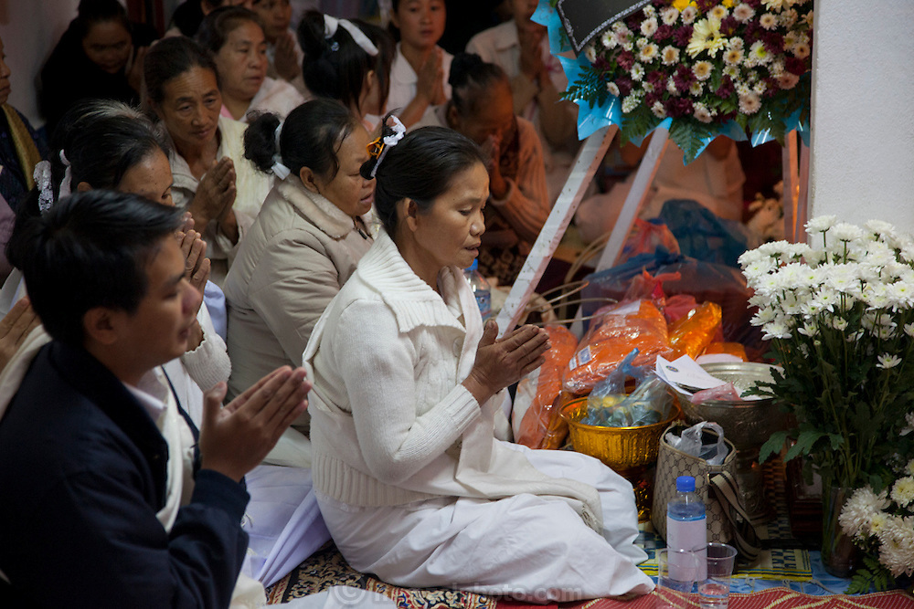 Funeral of Mr. Voua Sy Amkha, 63, at home in Ban Navieng Kham village, a suburb of Luang Prabang, Laos, and then cremation at the central crematorium site in Ban Vieng Mai. The propaganda official for the Lao government in Luang Prabang died of a stroke. His wife is in white in the center of the photo.