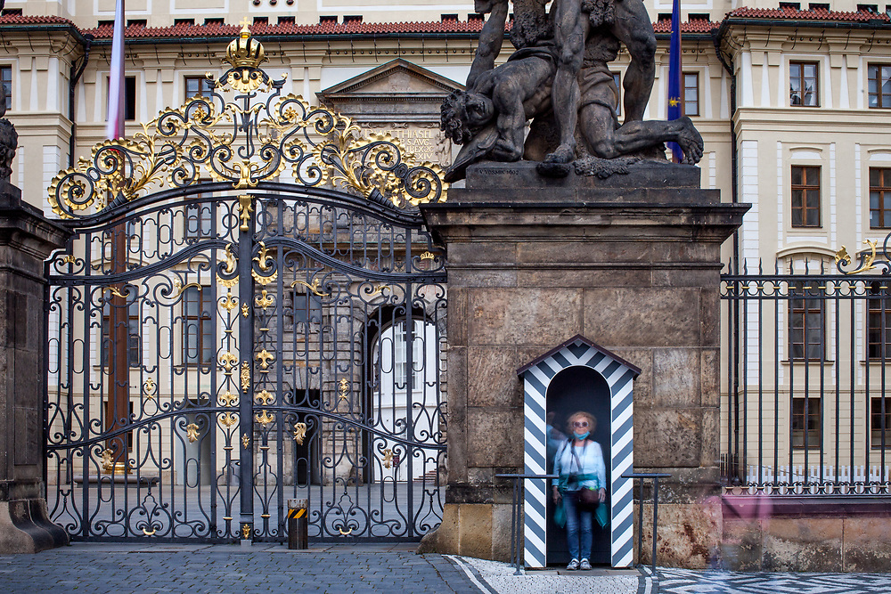 """A woman is getting  photographed inside the Prague Castle Guards house in-front of the Wrestling Titans (Sousoší Souboj Titánů) infront of empty Prague Castle at """"Hradcany Square"""" (Hradcanske Namesti). The Czech government lowered the security measures and as of Monday 25 May 2020, wearing of protective masks will be mandatory only in the interiors of buildings other than the place of residence and in public transport."""