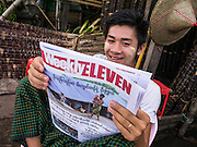 17 JUNE 2013 - YANGON, MYANMAR: A man reads a newspaper in a Yangon market. The Burmese newspaper industry has enjoyed explosive growth this year after private ownership was allowed in 2013. Private newspapers were shut down under former Burmese leader Ne Win in the early 1960s. The revitalized private press is a sign of the dramatic changes sweeping Myanmar, formerly Burma, in the last three years.      PHOTO BY JACK KURTZ