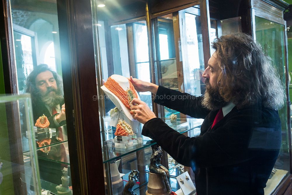 CATANIA, ITALY - 15 FEBRUARY 2016: Jeweler Massimo Izzo places a  a necklace made of 19th century coral from Sciacca (Southern Sicily) and yellow 18kt gold clamps with natural acquamarine from Brazil in a display cabinet in his boutique in Siracusa, Italy, on February 15th 2016. This necklace is part of the Jewels of the Sea collection.<br /> <br /> Massimo Izzo is a designer and creator of high-end jewelry inspired by Sicily and the Mediterranean culture.