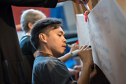 """26 July 2018, Amsterdam, the Netherlands: """"#PreventionNotCondemnation, """"#HealTheIlls"""". After morning prayers in the Interfaith Networking Zone, Ryan Mendoza from the Philippines writes a message on a symbolic bridge, expressing hopes and challenges for a coordinated response to HIV, particularly in view of the work against sexual and gender-based violence. The morning prayer was held on the theme of """"Faith against Gender based violence - Thursdays in Black"""". On 23-27 July 2018 in Amsterdam, the Netherlands, the World Council of Churches - Ecumenical Advocacy Alliance in collaboration with faith and other partners hosts an Interfaith Networking Zone in the International AIDS Conference's Global Village area, providing a dynamic space for exchanges, resources and workshops. The Global Village is an integral part and recurring feature of the International AIDS Conference, and offers an accessible venue intended to strengthen the connection between the international conference and the local hosting community."""
