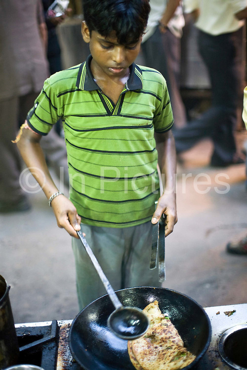 A boy cooks a paratha in a pan of oil at the famous Parawthe Wala restaurant in Old Delhi, India<br /> The parantha is an Indian fried bread, folded and filled with fillings and then fried.<br /> Gali Paranthe Wali or Paranthe wali Gali means the the street of fried bread and name of a narrow street in Chandni Chowk Old Delhi, noted for its series of shops selling paratha