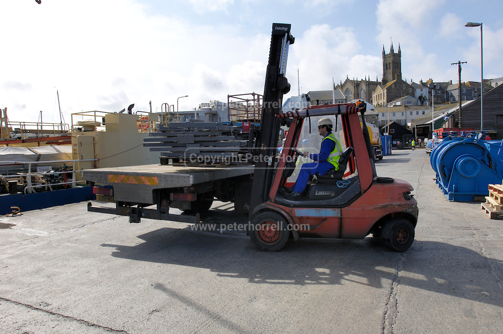 UK, Penzance - Monday, March 23, 2009: A forklift truck unloads the bell frames from the lorry. The frames and eight bells were ultimately loaded onto the Isles of Scilly Steamship Company's supply vessel the Gry Maritha for transportation to St Mary's on the Isles of Scilly. (Image by Peter Horrell / http://www.peterhorrell.com)