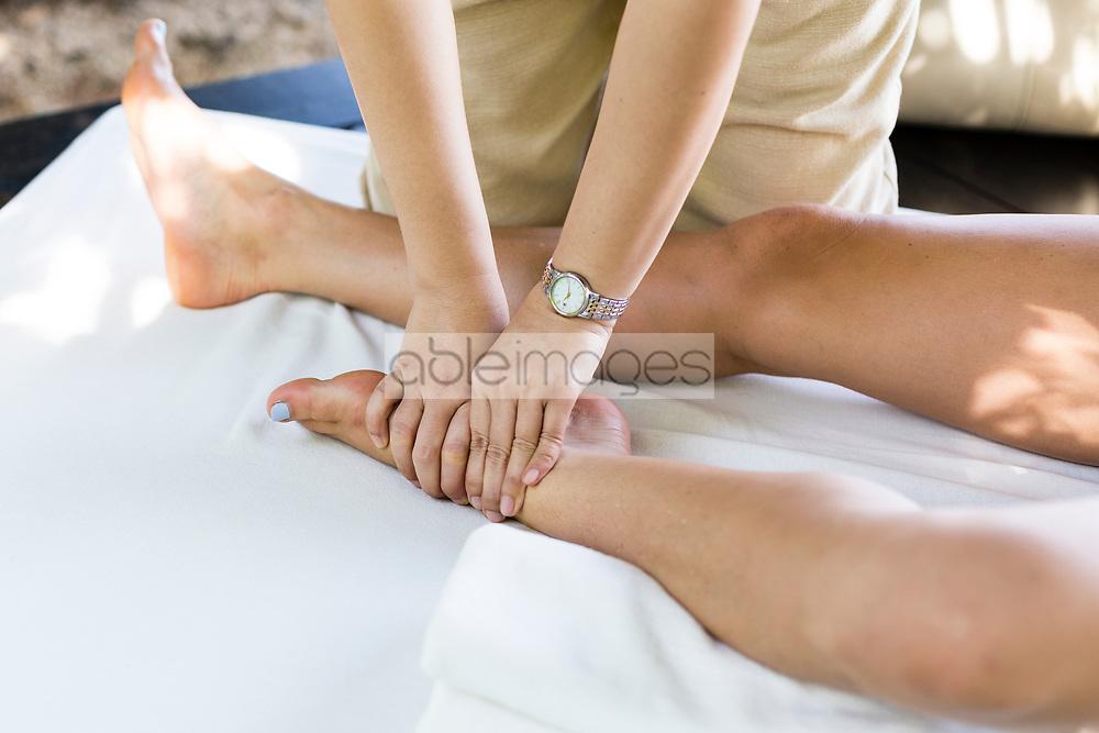 Massage Therapist Massaging Woman Foot Outdoors