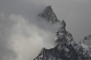 Storm clouds swirl around the 12,330 ft. summit of Teewinot Mountain, in Grand Teton N.P., Wyoming