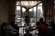 Giovani mangiano Chat intorno a un tavolo all'interno di un appartamento lussuoso. All'esterno, lo spettro dei nuovi edifici dell'area di Casanchis, una delle più trasformate dal piano di riqualificazione, Addis Ababa 11 settembre 2014.  Christian Mantuano / OneShot <br /> <br /> Young Ethiopians eating Chat around a table in a luxurious apartment. Outside, the specter of the new buildings in the Casanchis area, one of the most transformed by the renewal plan, Addis Ababa September 11, 2014.