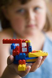 Nursery school girl holding up a Lego model she has made,
