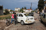 Two Turkish boys look at a Syrian car after it was attacked after two car bombings in the Turkish border town of Reyhanli