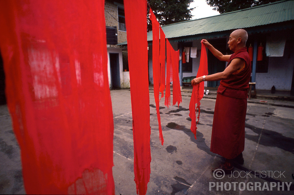 DHARAMSALA, INDIA -  A monk hangs freshley dyed ceremonial cloth at the Namgyal Monastery, inside the Dalai Lama's compound in Dharamsala, India. The focus of cultural life in Dharamsala is the Namgyal Monastery, the tantric college which performs rituals with and for His Holiness the Dalai Lama. The Namgyal Monastery was founded by the Third Dalai Lama in the late sixteenth century. Since then, the monastery has exclusively served the Dalai Lamas. A distinctive feature of this monastery is its diversity of practice: prayers and rituals of all the major schools of Tibetan Buddhism are performed by Namgyal monks. The monastery is now situated next to the Tsuglag Khang, or the Central Cathedral, across from the Dalai Lama's residence. Young monks can often be seen studying, and practicing debate in the courtyard leading to His Holiness' residence. At present, the monastery has more than 180 monks, of which the younger monks study the major texts of Buddhist Sutra and Tantra.(PHOTO © JOCK FISTICK)