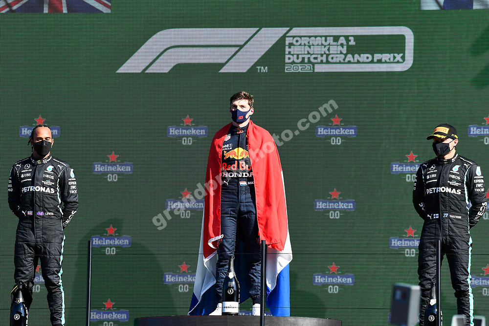 Max Verstappen (Red Bull-Honda) with Dutch flag on the podium with Mercedes drivers Lewis Hamilton and Valtteri Bottas  after the 2021 Dutch Grand Prix in Zandvoort Photo: Grand Prix Photo