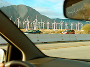 A cluster of electricity generating windmills seen from the car. California USA.