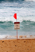 Warning sign and tattered flag on beach. Oahu, Hawaii