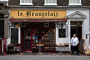 Member of restaurant staff taking a cigarette break outside Le Beaujolais wine bar on 18th February 2020 in London, England, United Kingdom. On the ground floor, Le Beaujolais is Londons oldest French wine bar whilst downstairs resides a restaurant and members only Club. Le Beaujolais is proud of its French tradition, which since 1972 has been providing a genuinely French atmosphere, in a little piece of France tucked away in the heart of London.