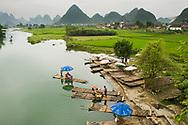 Tourists float the Li River on bamboo rafts year Yangshuo, China.