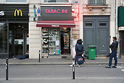 """March, 21st 2020 - Paris, Ile-de-France, France: Parisians queueing up with proper social distance whilst buying from shops and kiosks, in the hope of protecting themselves from the spread of the Coronavirus, during the fifth day of near total lockdown imposed in France. Almost a week after President of France, Emmanuel Macron, said the citizens must stay at home from midday on Tuesday for at least 15 days. He said """"We are at war, a public health war, certainly but we are at war, against an invisible and elusive enemy"""". All journeys outside the home unless justified for essential professional or health reasons are outlawed. Anyone flouting the new regulations would be punished. Nigel Dickinson"""